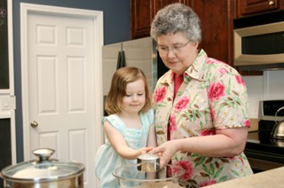 Grandmother showing grand daughter how to bake a cake